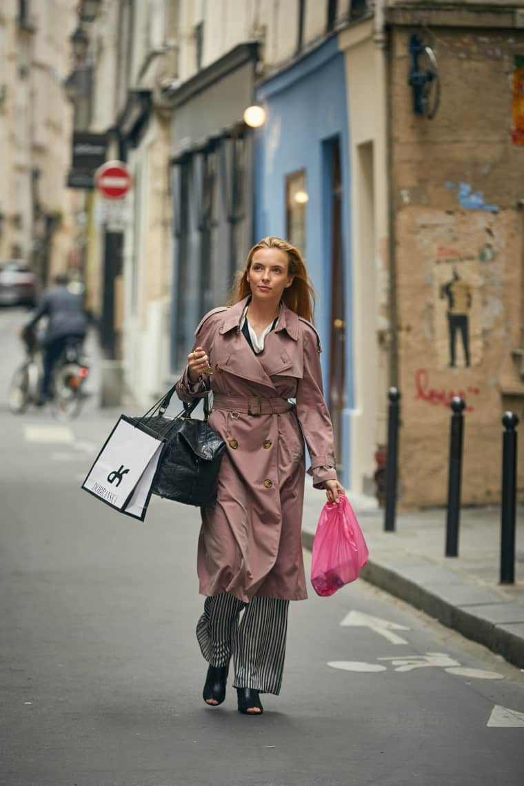 Villanelle goes on a shopping spree following a successful kill in Vienna, dressed in a Burberry Mac coat, Lanvin blouse, and Balenciaga boots.