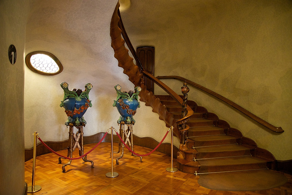the spiny wooden staircase flanked by two Gaudi designed vases