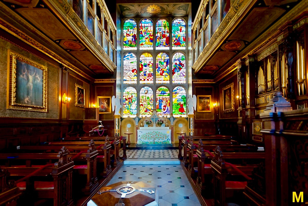 stained glass windows and pews in the chapel of Hatfield House