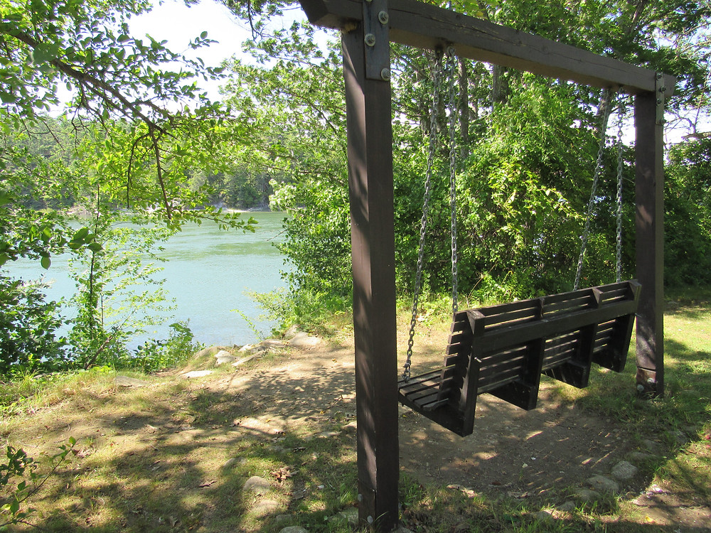 A wooden swing bench facing the Damariscotta River in Maine
