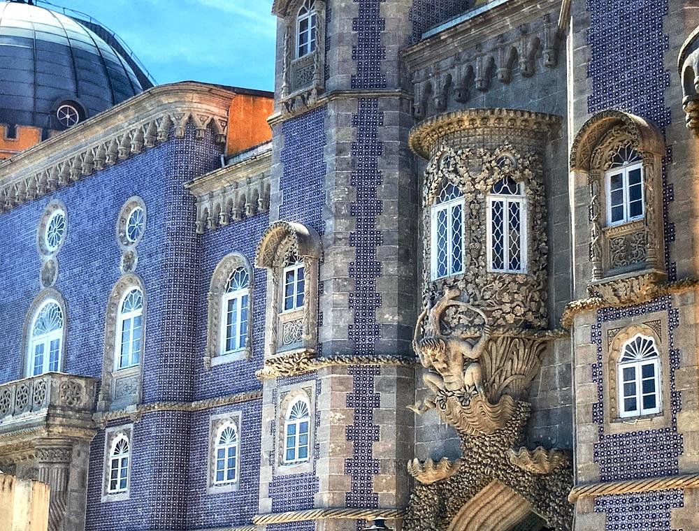 blue tiled facades of Pena Palace and the merman gargoyle over an entryway