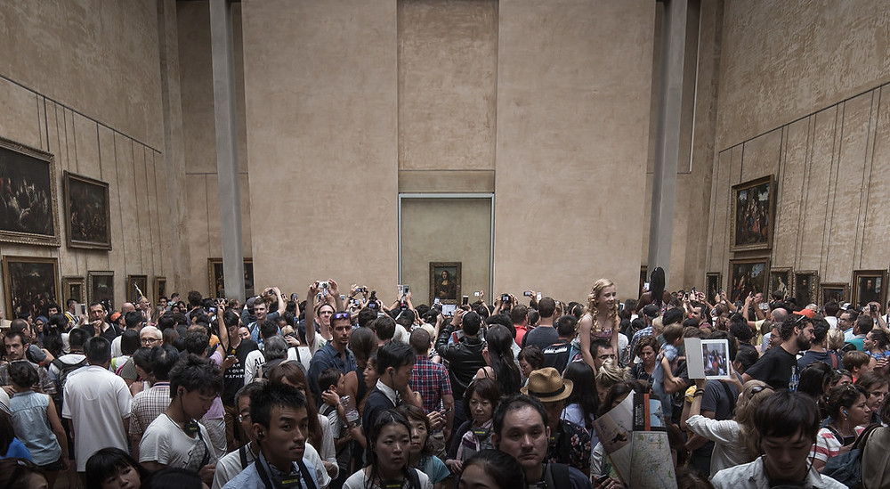 massive crowds in front of the very small Mona Lisa at the Louvre