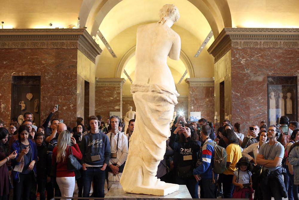 tourists crowded around Venus de Milo at the Louvre