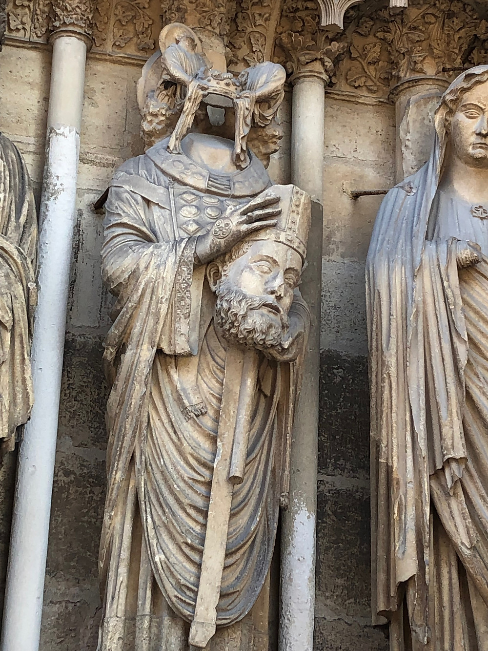 St. Denis holding his head on the facade of Reims Cathedral