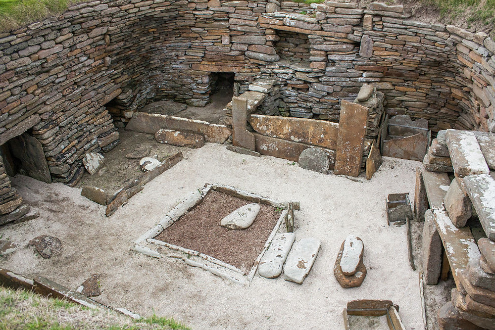 a home in Skara Brae were you can see beds, a dresser, and the central fireplace