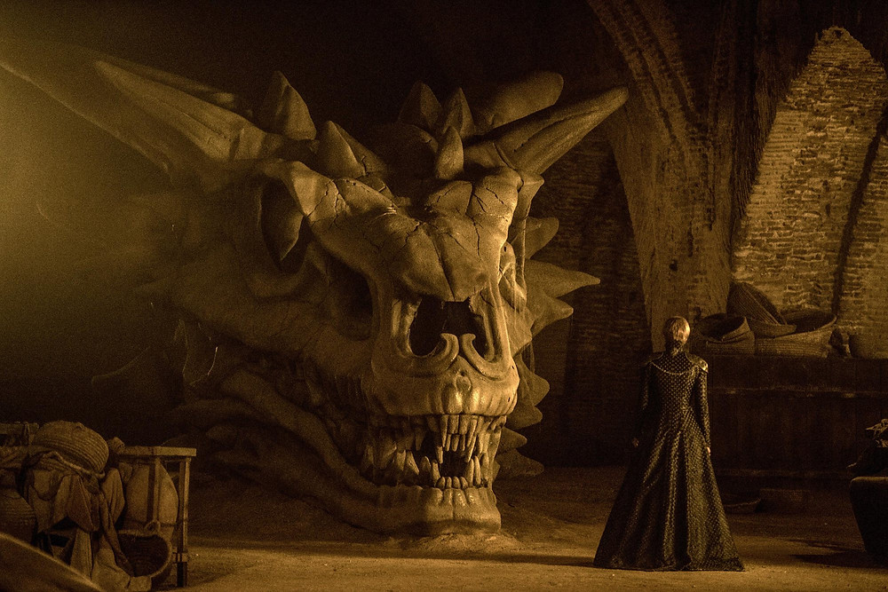 Cersei contemplates a dragon skull in the Red Keep while Qyburn prepares to demonstrate his new dragon slaying weapon