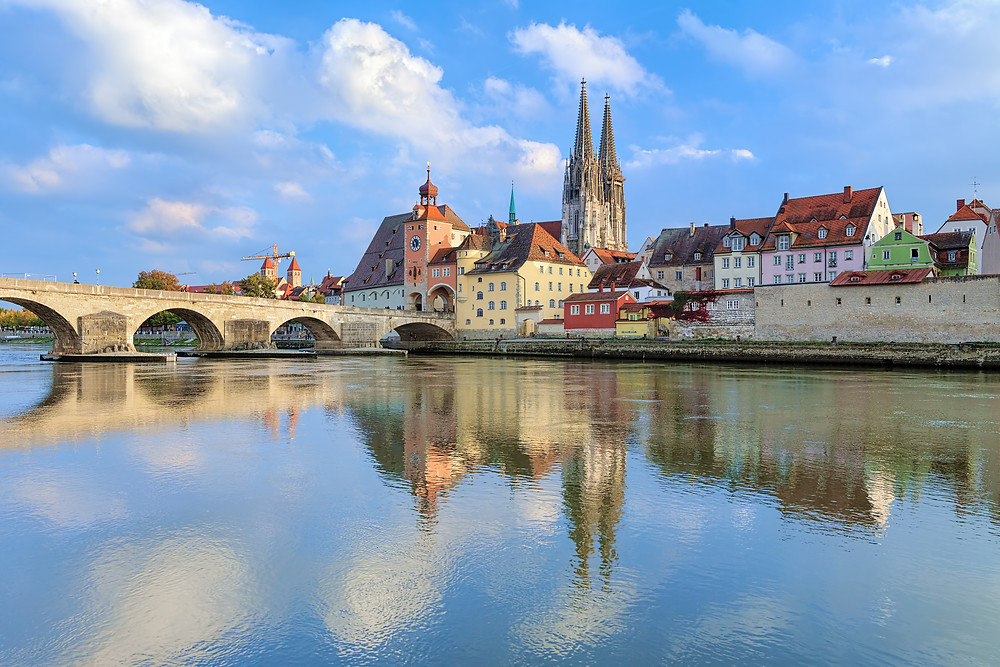 the stone bridge and old town of Regensburg, as seen from the banks of the Danube River
