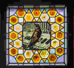 stained glass window with a bird playing a piano in El Capricho
