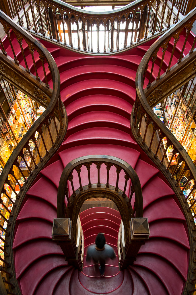 the iconic red staircase of Livraria Lello