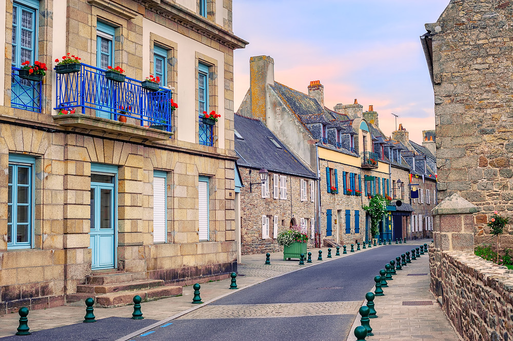 Traditional french stone houses with blue windows decorated with red flowers in