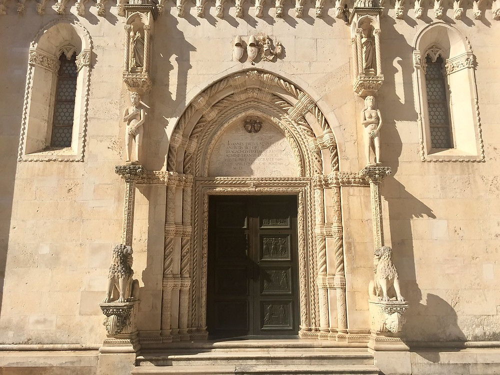 The entrance to Sibenik Cathedral. Adam and Eve appear almost embraced to be naked.