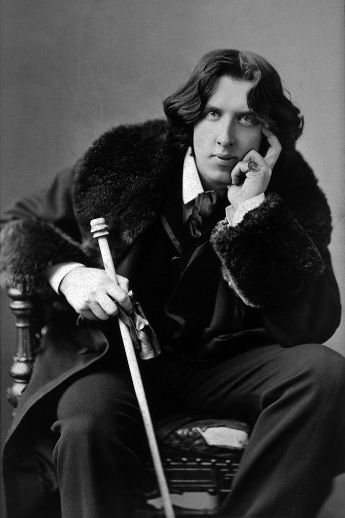 the novelist and playwright Oscar Wilde, in a languid pose in his famous velvet jacket