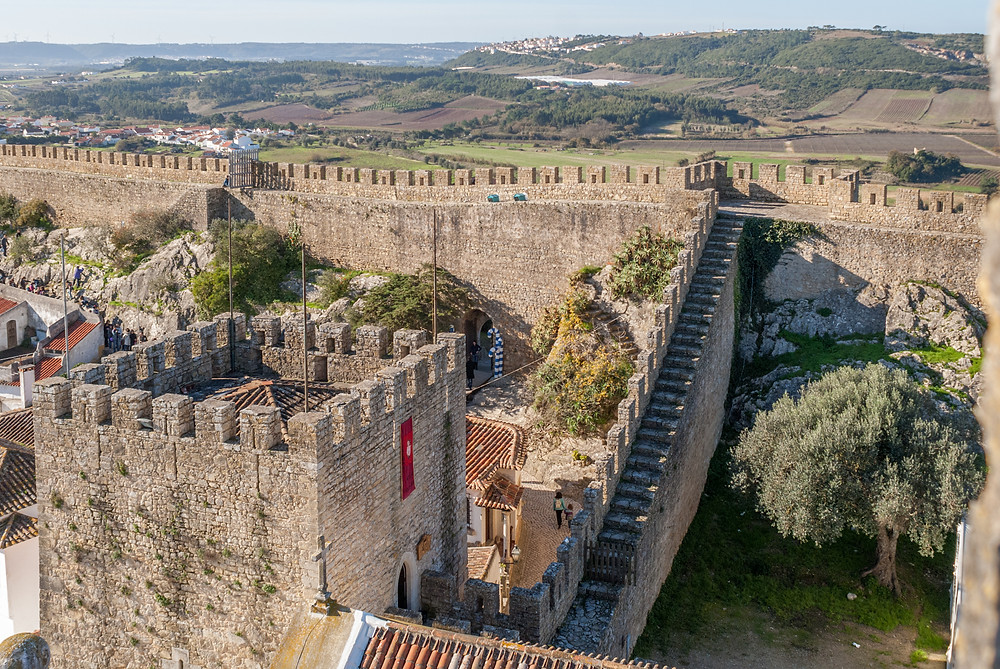 The city walls of Obidos -- oh, how I would've loved to scamper up them. Public domain photo