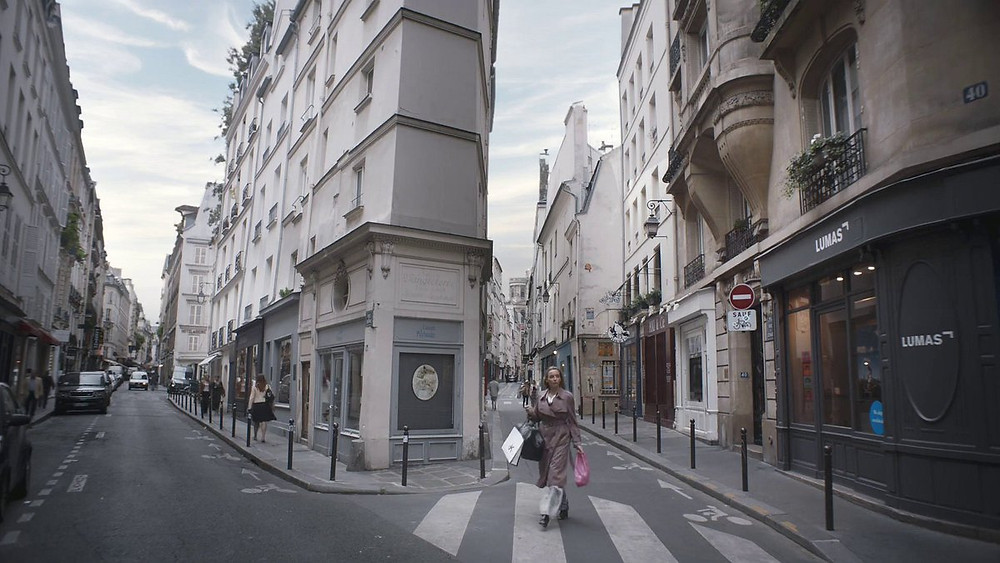 Villanelle walking at the intersection of Rue de l'Echaudé and Rue de Seine, past the tony art gallery Lumas