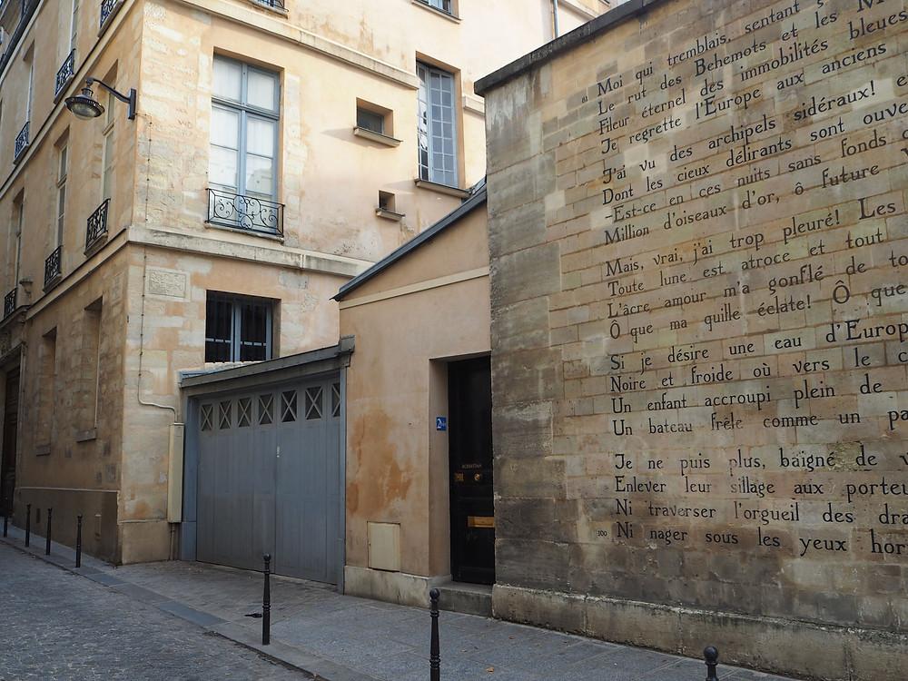 Le Bateau Ivre poem inscribed on a stone street wall on rue Ferou