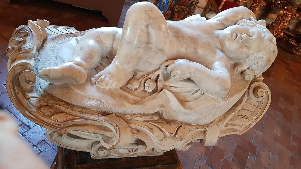 a sleeping putti sculpture in the Galleria Spada