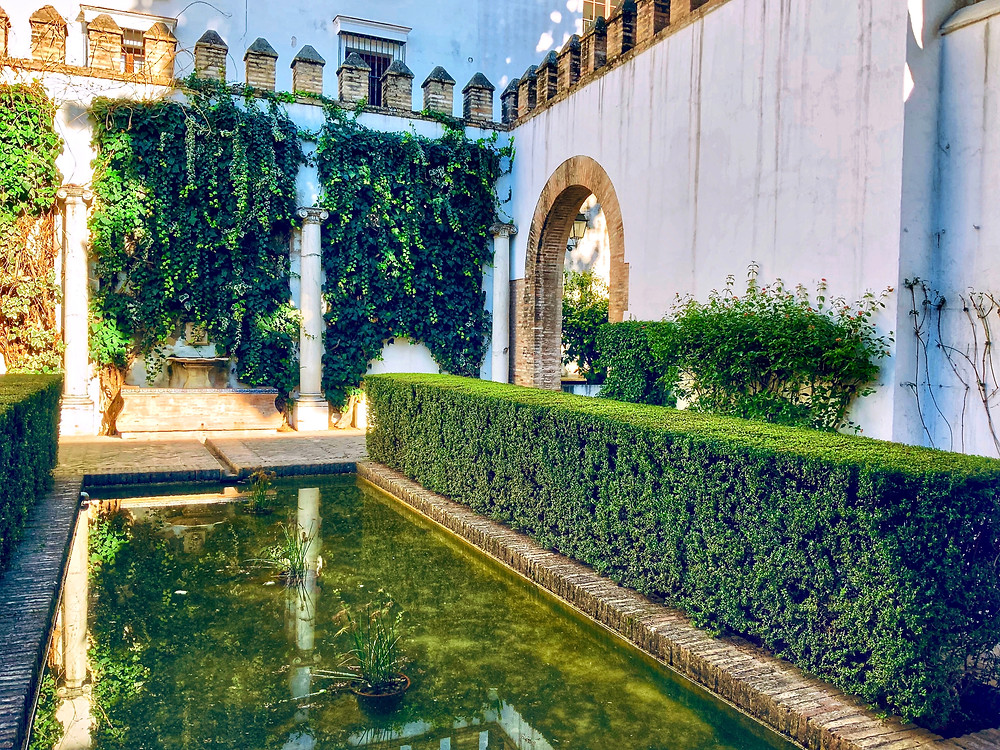the Levies Courtyard with its small reflecting pond in the Alcázar gardens