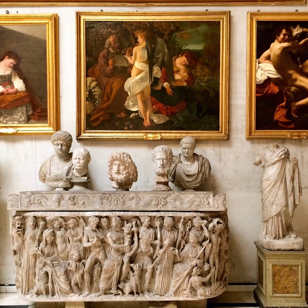 sculptures in the Aldobrandini Room of the Doria Pamphilj, with a famous Caravaggio painting above
