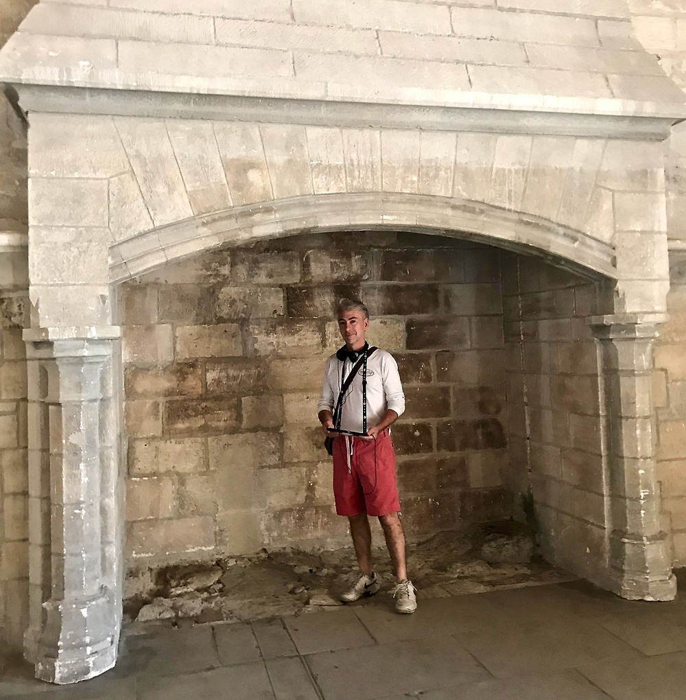 my travel partner standing in a massive stone fireplace with histopad in hand