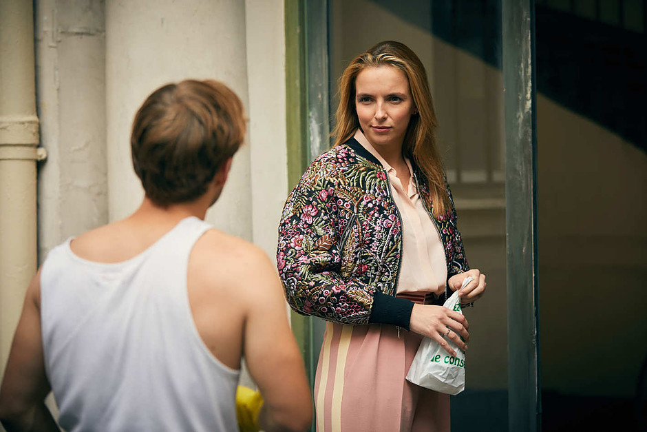 Villanelle, wearing a hip Phillip Lim flowered bomber jacket, meets her awestruck neighbor Sebastian coming home to her apartment