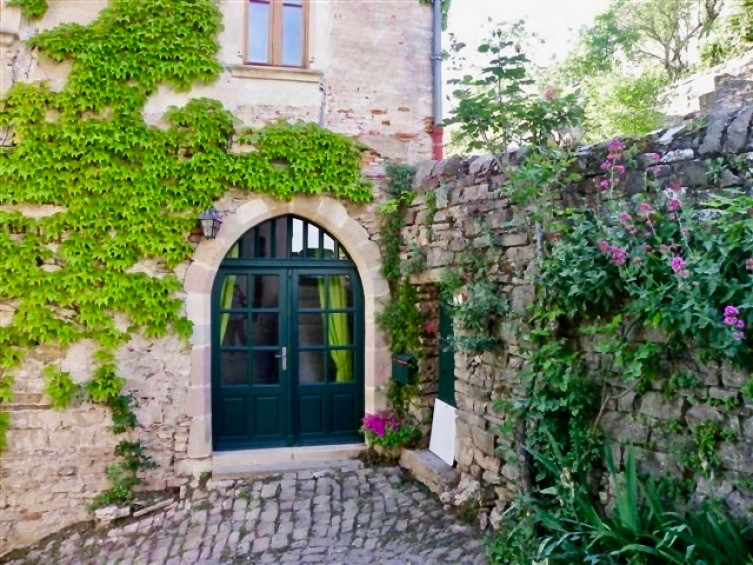 a beautiful stone wall and arched door in Cordes sur Ceil