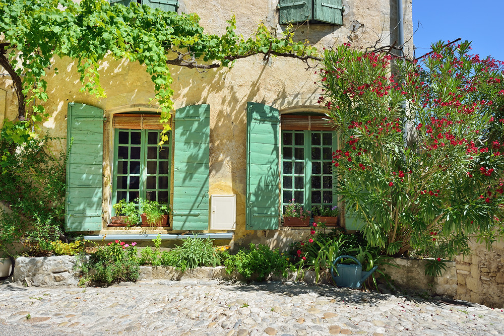 typical cute stone house with colorful shutters in Vaison-la-Romaine France