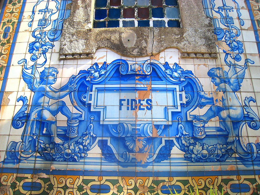 """detail of the facade and its """"faith"""" tile"""