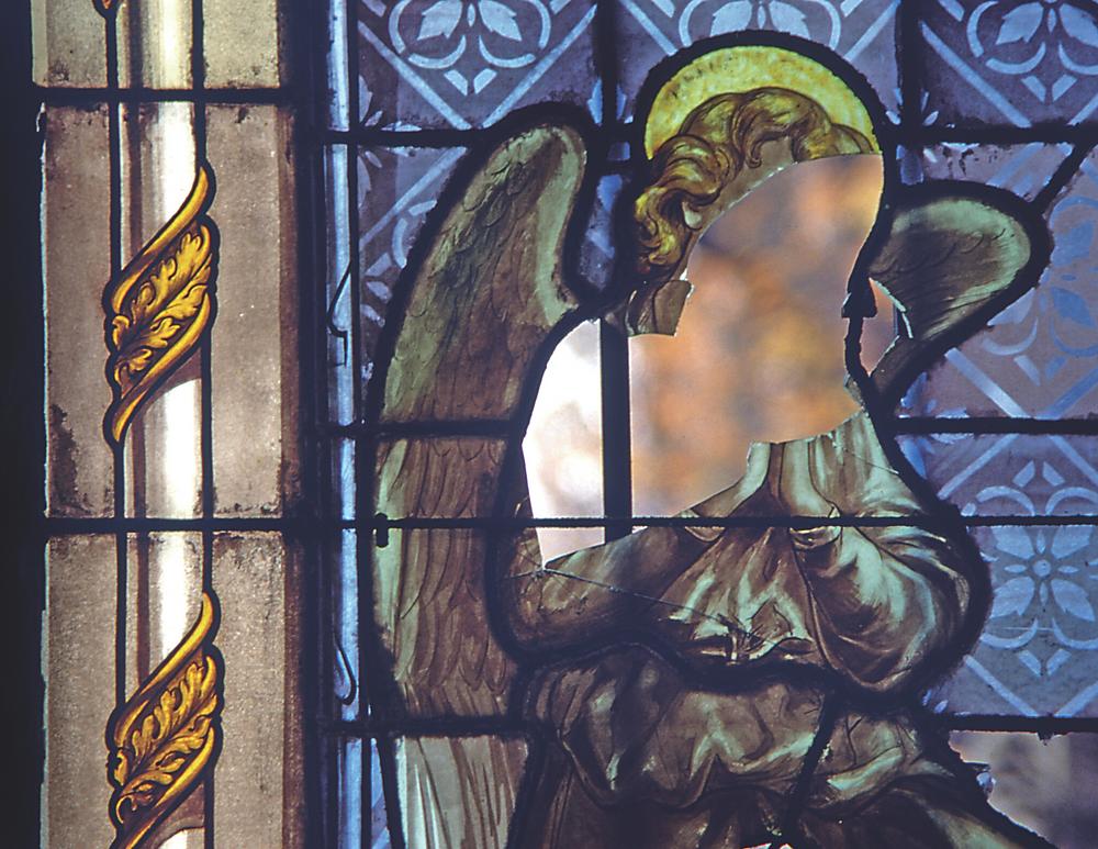 broken stained glass window in a mausoleum