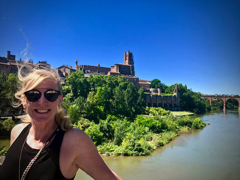 happy on the Pont Vieux in Albi France, with the Berbie Palace in the background