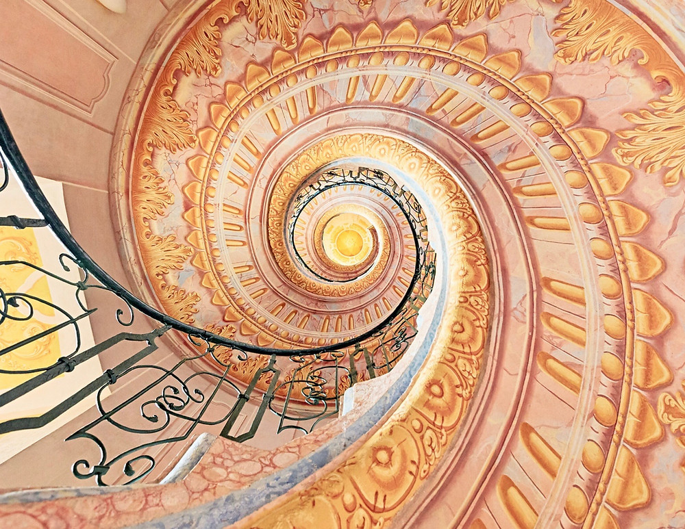 the beautiful pink and gold spiral staircase connecting the library to the church in Melk Abbey