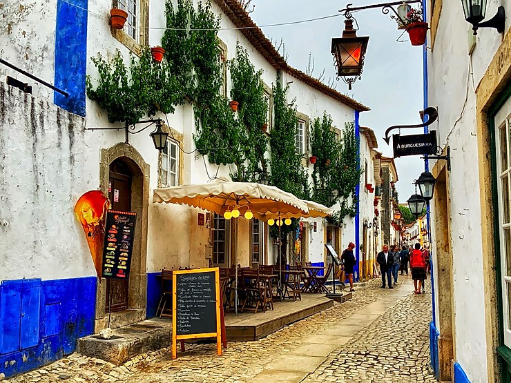 Rue Direita in Obidos Portugal, lined with artisan shops and cute little eateries