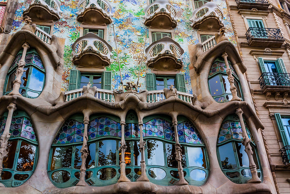 the gorgeous facade of Casa Battlo, with mask-like balconies, a dragon-like skin of ceramics, and shin bones columns in the window