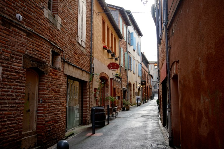 a main street in Albi France with the Albi Cathedral in the background