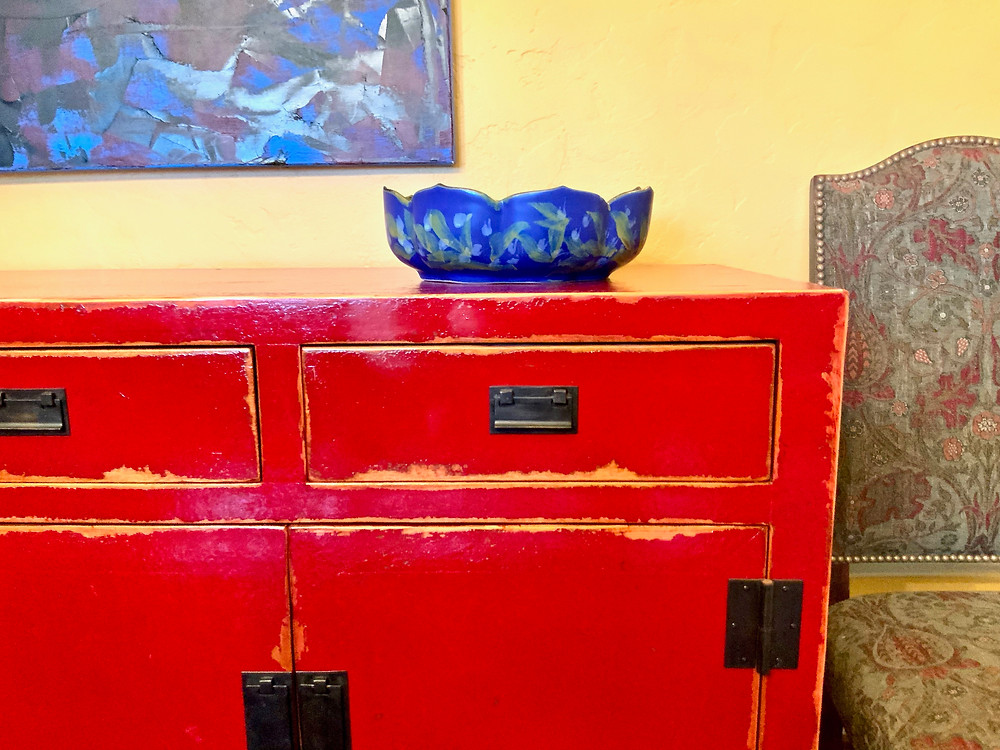 a beautiful arts and crafts bowl that I purchased in the museum shop, on top of my Asian inspired dining room buffet