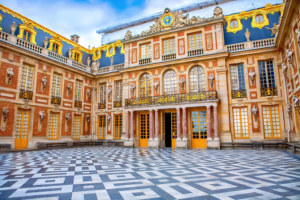the Marble Court of Versailles, with the king's quarters fronted by a gold balcony and eight marble columns