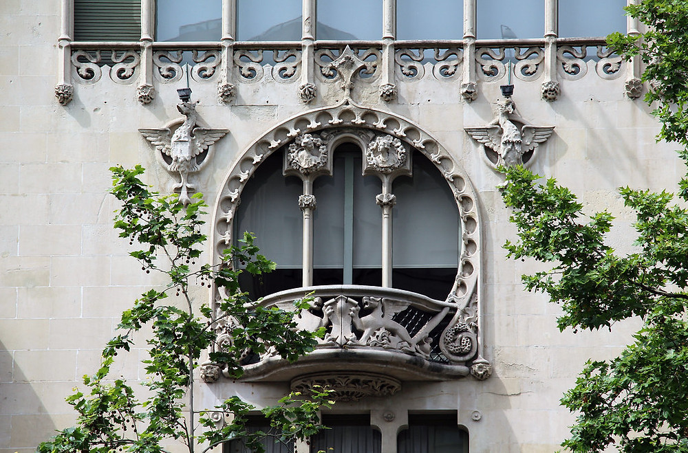 a lovely rounded balcony on the third floor, flanked by winged griffins