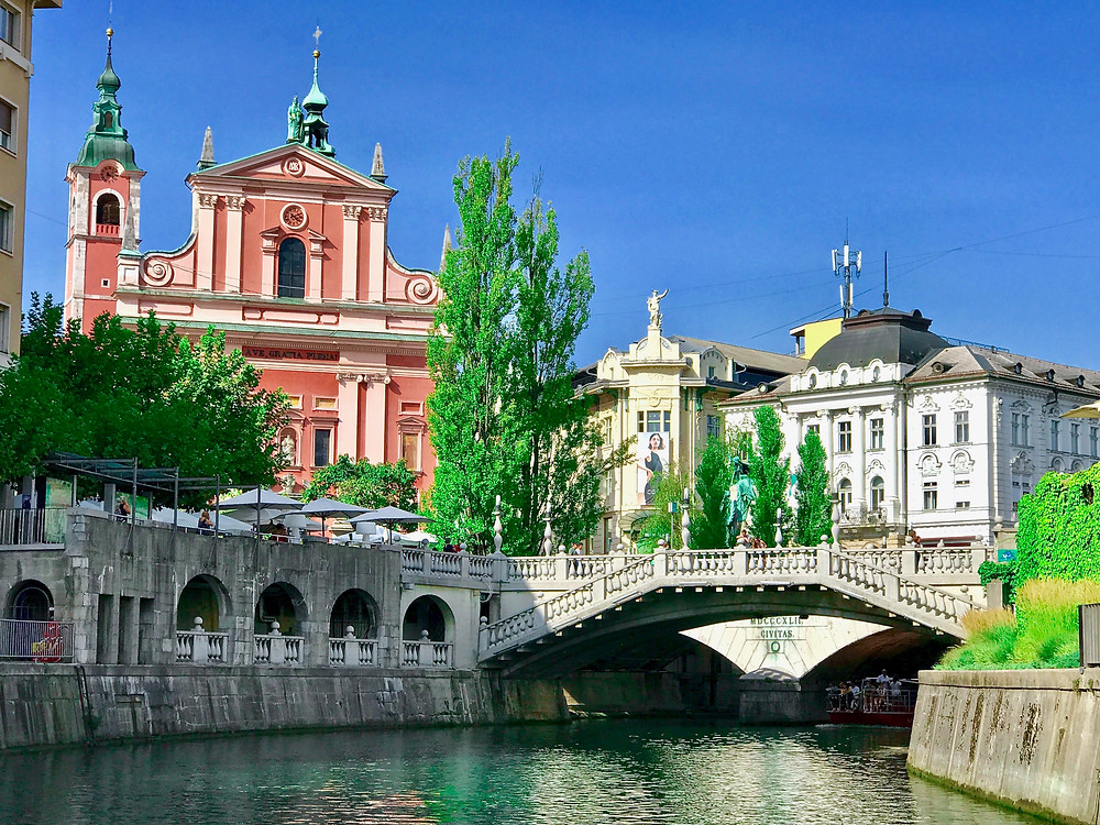cafes line the leafy banks of the emerald green Ljubljanica River