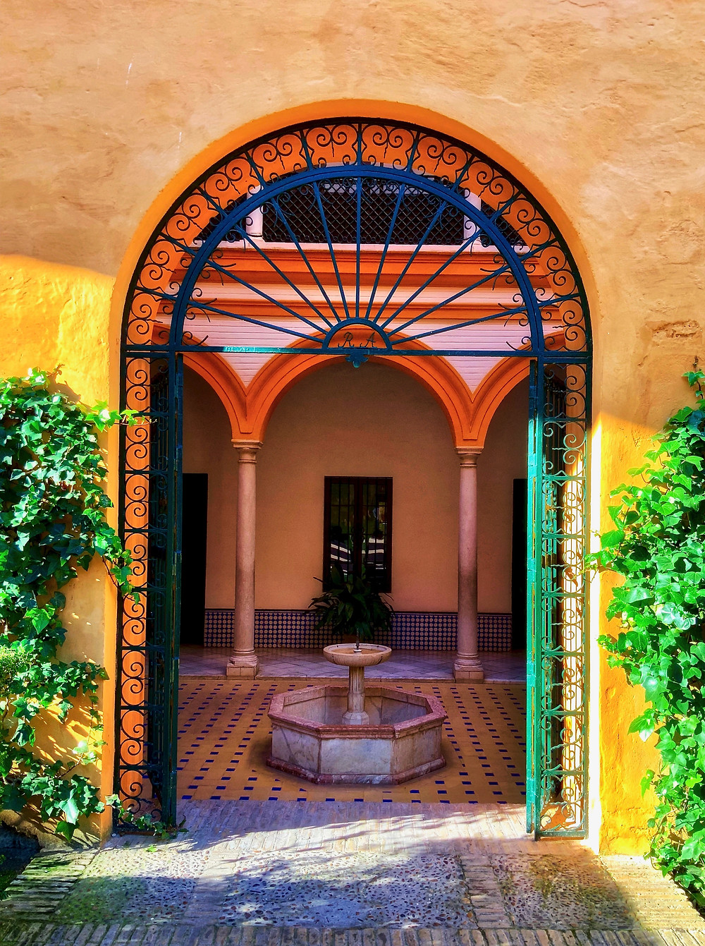 a beautiful orange hued doorway in the Alcazar Gardens in Seville