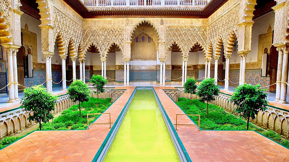 Courtyard of the Maidens with its long reflecting pool in the Royal Alcázar of Seville, a must see site in Andalucia