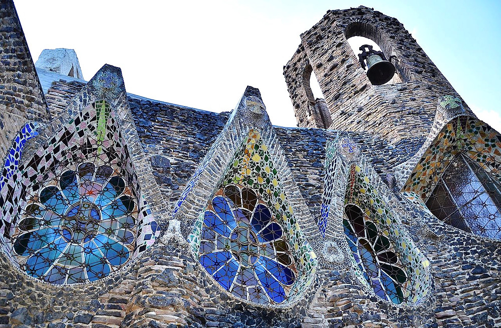 pointy arches and floral stained glass windows on the crypt of Colonia Güell