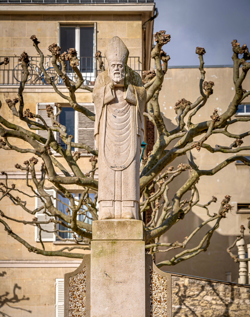 statue of Saint Denis carrying his head on Place Suzanne-Buisson, a hidden gem in Montmartre