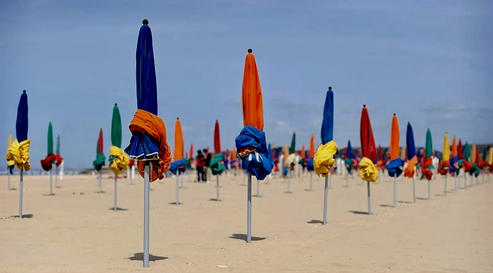 the forest of colorful umbrellas that are permanent fixtures in Deauville