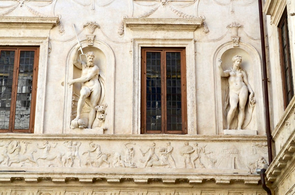 stucco statues of pagan deities Pluto and Persephone decorate walls in the ground floor courtyard