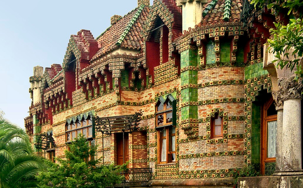 the colorful facade of Gaudi's El Capricho in Comillas, encrusted with sunflowers