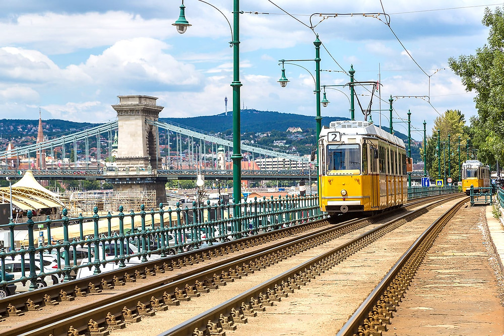 a tram with Chain Bridge in the background