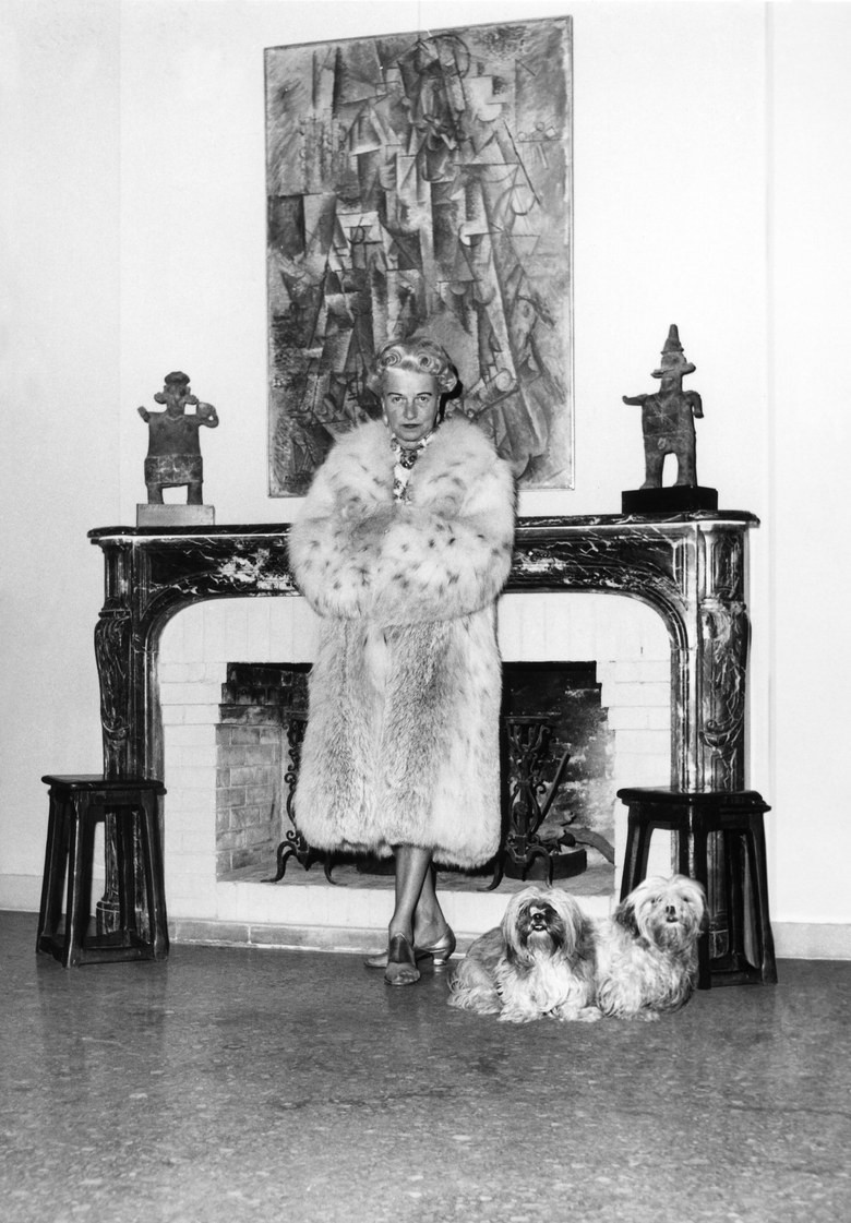 Peggy Guggenheim standing in her fur in front of a Braque paintings