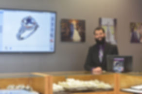 Custom jewelry design session at Thurber Jewelers. Desiger at computer with ring design on TV screen. Jewelry showroom and custom design.