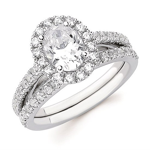 White gold engagement ring with oval cut diamond center and diamond halo. Diamond accented band. Matching wedding band.