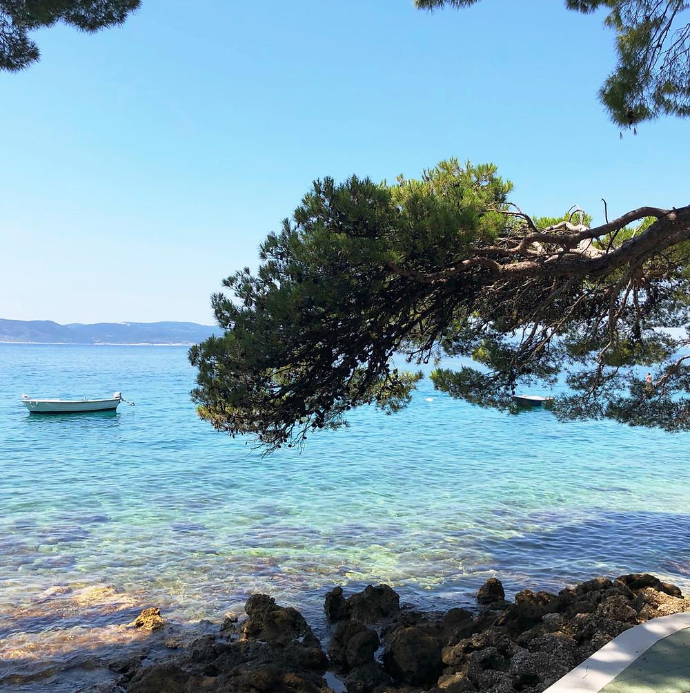 Strandpromenad med turkost hav och roddbåt