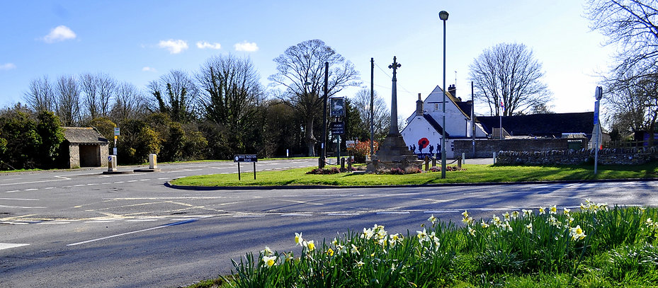 View of The White Hart pub on the corner of Burford Road on a sunny day in the village